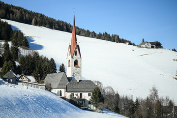 Catholic church in the Italian dolomites in wintertime with snow. San Volfango church in Sorafurcia, South Tyrol, Italy. Tower bell