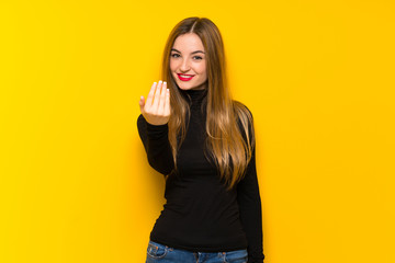 Young pretty woman over yellow background inviting to come with hand. Happy that you came