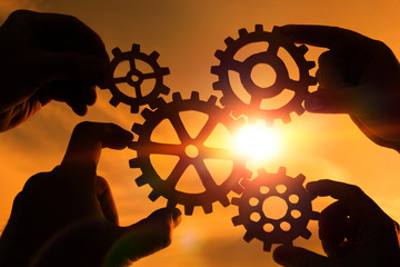 Gears in the hands of people on the background of the evening sky. mechanism.  the concept of teamwork.