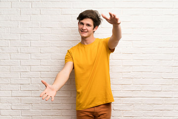 Teenager man over white brick wall presenting and inviting to come with hand