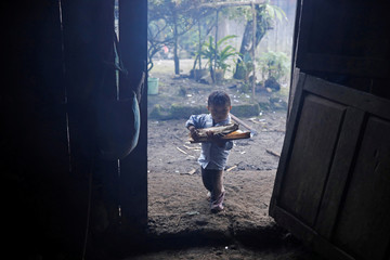 Oliver Gomez, brother of Felipe Gomez Alonzo, a 8-year-old boy who fell ill and died in the custody of U.S. Customs and Border Protection, carries firewood towards his home in Yalambojoch