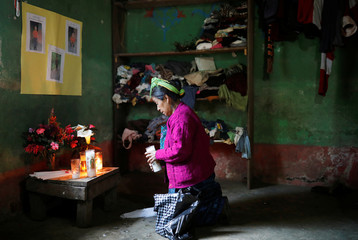 Catarina Perez, grandmother of Felipe Gomez Alonzo, a 8-year-old boy who fell ill and died in the custody of U.S. Customs and Border Protection, prays at an altar in memory of Felipe at the family's home in the village of Yalambojoch