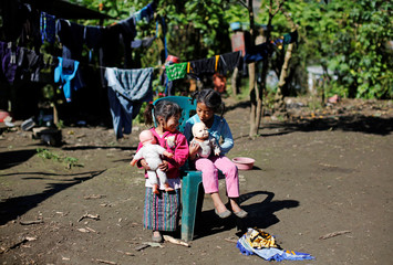Children play with dolls near the house of Felipe Gomez Alonzo, a 8-year-old boy who fell ill and died in the custody of U.S. Customs and Border Protection, in the village of Yalambojoch