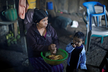 Catarina Alonzo, mother of Felipe Gomez Alonzo, a 8-year-old boy who fell ill and died in the custody of U.S. Customs and Border Protection, dekernels maize at her home in the village of Yalambojoch