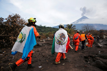 """Members of the Mexican rescue team, known as """"the Topos"""", holding a Guatemala and Mexican flags, walk at an area  affected by the Fuego volcano at San Miguel Los Lotes"""