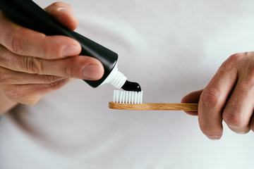Man with a black toothpaste and a bamboo toothbrush