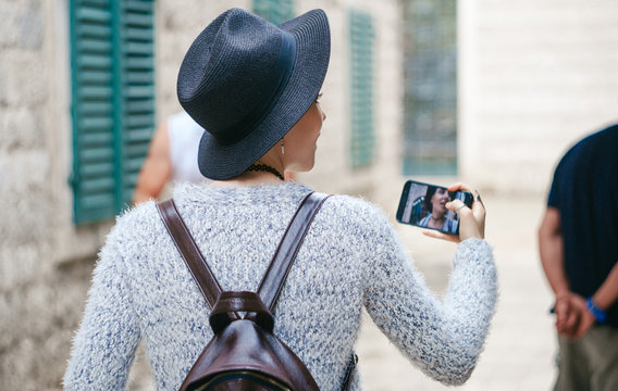 A girl in a black hat with backpack walks around a European city and Shoots video on a smartphone. Traveling, tourism, couchsurfing, education abroad