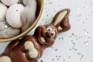 Easter. Easter eggs in a wooden box. Silver. Bokeh. Chocolate Bunny smiles. Easter Bunny