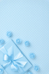 Springtime decorated blue gift box and rose flowers top view for 8 March Women day copy space on pastel blue paper background. Mother day template with present box. Flat lay. Springtime collection