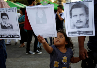 A child looks at a picture of a person who disappeared during Guatemala's civil war at an demonstration against the former Guatemalan military dictator Efrain Rios Montt, who died on Sunday at aged 91, in Guatemala City