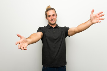 Blond man with long hair over white wall presenting and inviting to come with hand