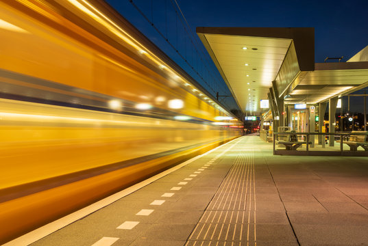 Train leaving the platform on a train station in the evening. Groningen, Holland.