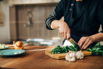 Female chef chopping raw vegetables on a wooden board