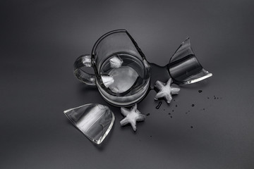 Broken glass cup with water and ice on a black background
