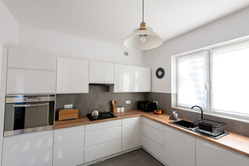 Minimal white kitchen interior with wooden countertop. Real photo