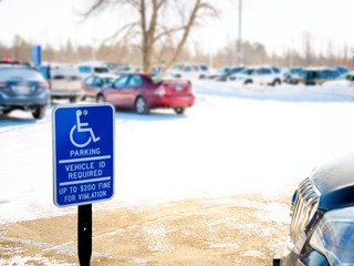 Handicapped parking sign posted in snow covered parking lot of a medical facility in winter.