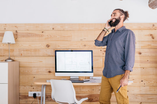 Happy young architect in office at home talking on the phone