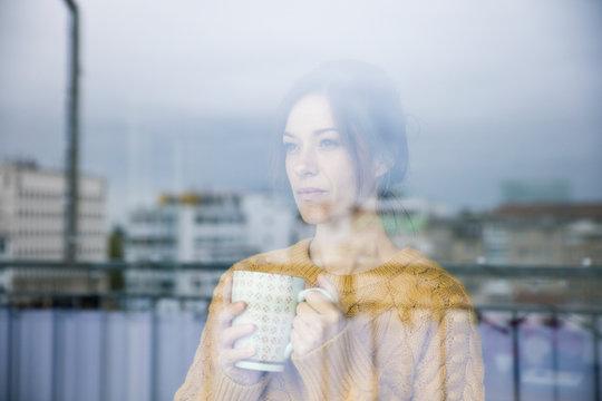 Sad woman standing at the window, drinking tea