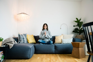 Mature woman sitting cross-legged on couch with eyes closed, meditating at home