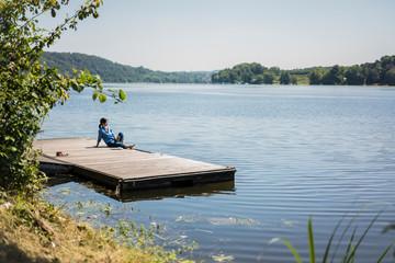 Mature woman sitting on a jetty at a lake, taking a break