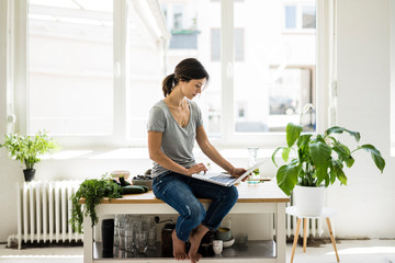 Woman sitting on kitchen table, searching for healthy recipes, using laptop