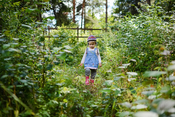 Little girl wearing knitted hat and denim shirt in nature