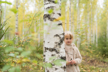 Portrait of blond girl playing in birch forest
