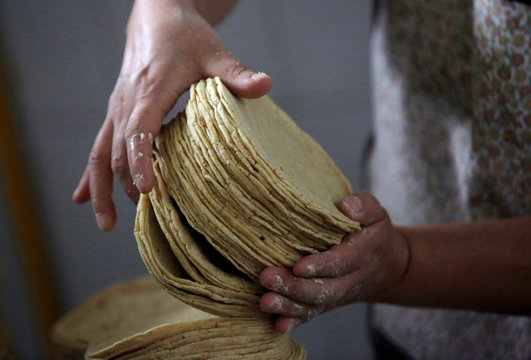 An employee arranges a stack of freshly made corn tortillas at a tortilla factory in Mexico City