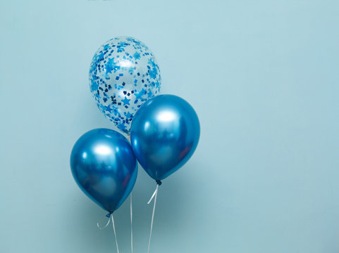 bright matte balloons on a blue background.  three blue inflated balloons. stylish party with balloons. round blue and transparent  balloon. place of celebration