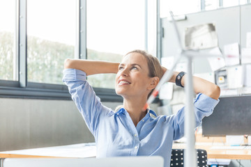 Smiling woman in office with wind turbine model in foreground