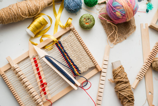 Tools for weaving and thread lie on a white table