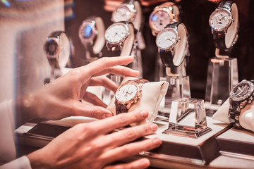 Close-up of the seller's hand shows the exclusive men's watch from the new collection in the luxury jewelry store