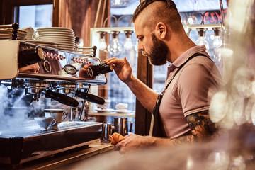 Fototapeta Handsome barista in uniform preparing a cup of coffee for a customer in the coffee shop obraz