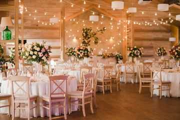 Coziness and style. Modern event design. Table setting at wedding reception. Floral compositions with beautiful flowers and greenery, candles, laying and plates on decorated table.