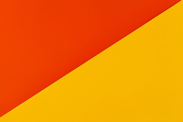 Wall Mural - Vibrant orange and yellow colored plastic surfaces jointed diagonally, background.
