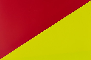 Wall Mural - Vibrant red and lime colored plastic surfaces jointed diagonally, background.