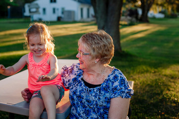 Grandmother with cute granddaughter sitting on bench in park during sunset