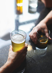 Hands holding a glass of beer at a table in a bar