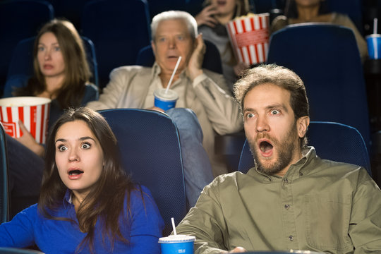 Mature couple watching a horror movie at the cinema