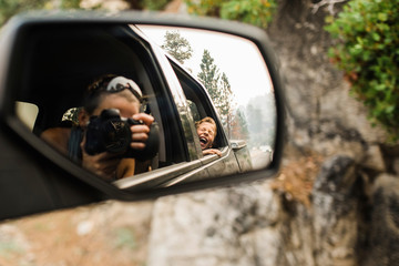 Son screaming while mother photographing with camera reflecting on side-view mirror