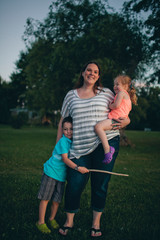 Portrait of smiling mother with cute children standing on grassy field against trees in park during sunset