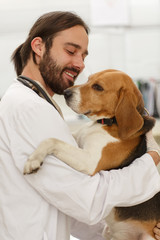 Adult man holding adorable dog and smiling.