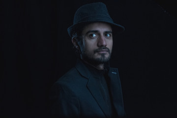 dark portrait of a young man with hat