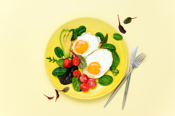 Fried eggs with spinach tomatoes and greens
