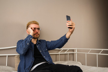 A young guy takes pictures of himself on the phone
