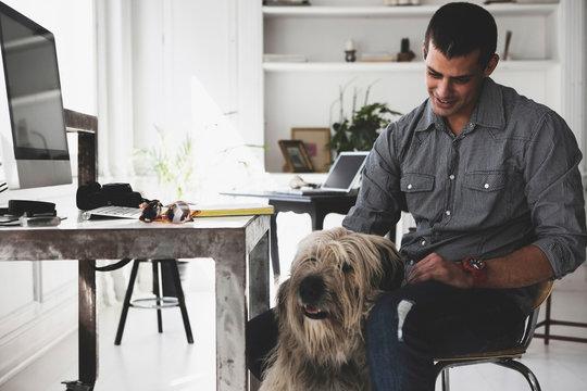 Young man sitting at desk stroking dog