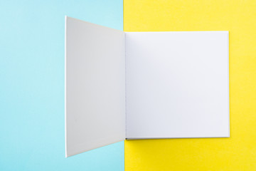 opened white square notebook on yellow and blue
