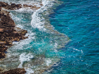 Clear blue sea at the edge of rocky shores