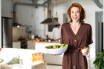 Friends preparing dinner party in the kitchen, woman serving salad