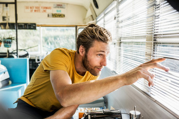 Young man looking through window blinds while sitting in bus